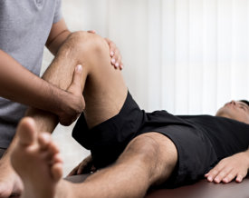 therapist treating injured knee of athlete male patient