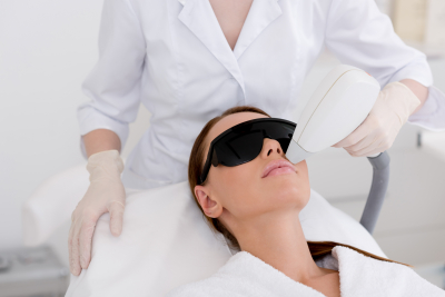 partial view of young woman receiving laser hair removal epilation on face