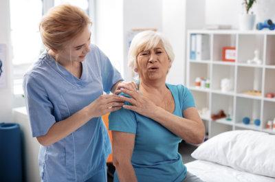 female therapist touching senior woman's shoulder